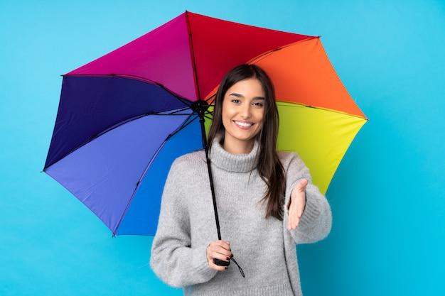 Jonge donkerbruine vrouw die een paraplu over geïsoleerd blauw muurhandenschudden na goede deal houden Premium Foto
