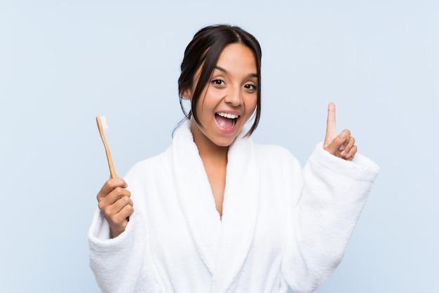 Jonge donkerbruine vrouw die in badjas haar tanden over geïsoleerde blauwe muur borstelt die een groot idee benadrukken Premium Foto