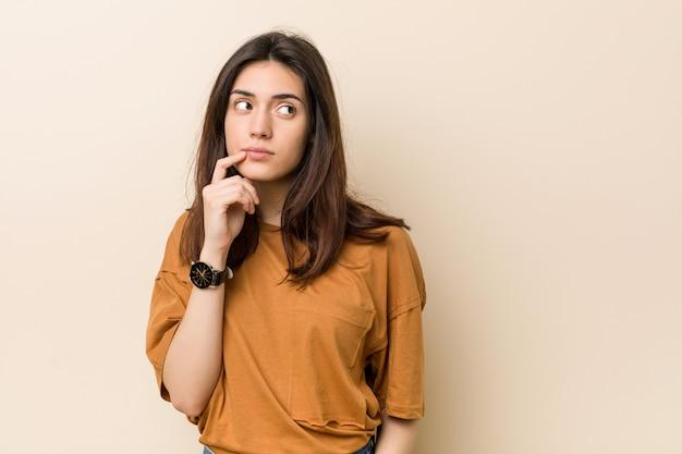 Jonge donkerbruine vrouw die zijdelings met twijfelachtige en sceptische uitdrukking kijkt. Premium Foto