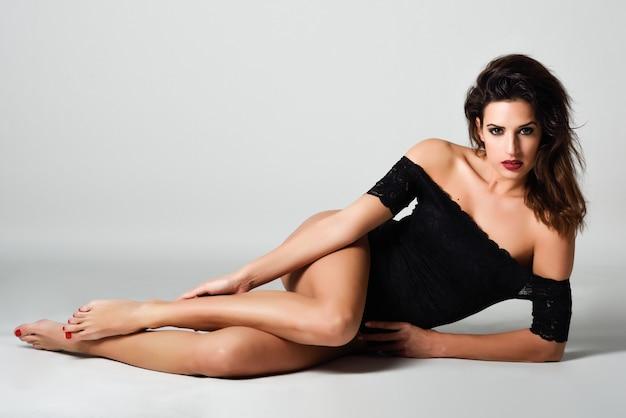 Jonge donkerbruine vrouw in zwarte lingerie die op de vloer ligt. Gratis Foto