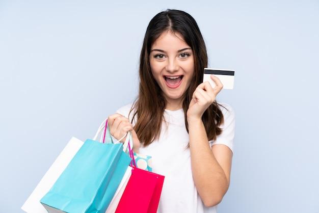 Jonge donkerbruine vrouw over blauwe het winkelen van de muurholding het winkelen zakken en verrast Premium Foto