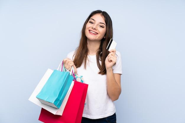 Jonge donkerbruine vrouw over blauwe muur met boodschappentassen en een creditcard Premium Foto
