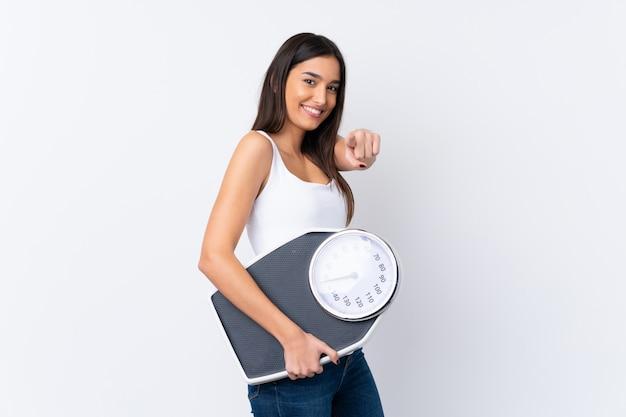 Jonge donkerbruine vrouw over geïsoleerde witte muur die een weegmachine houdt en aan de voorzijde richt Premium Foto