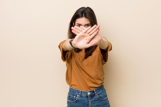 Jonge donkerbruine vrouw tegen een beige die een ontkenningsgebaar doet Premium Foto