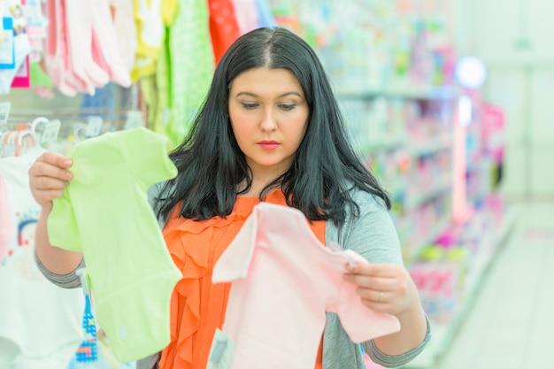 Jonge donkerbruine vrouwenmoeder die en kinderenoverhemden bekijken kleden bij kledingswinkel Premium Foto