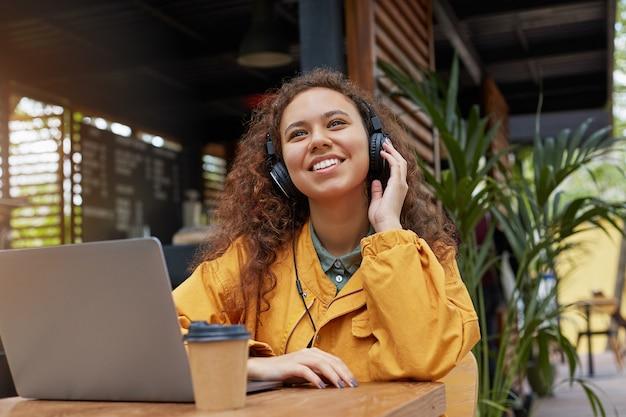 Jonge donkere gekrulde student vrouw zitten op een terras van een café, luistert naar muziek en droomt van een weekendfeest, gekleed in een gele jas, koffie drinken, werkt op een laptop. Gratis Foto
