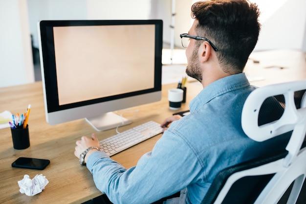 Jonge donkerharige man werkt met een computer op zijn bureaublad in kantoor. hij draagt een blauw shirt en ziet er druk uit. uitzicht vanaf de achterkant. Gratis Foto