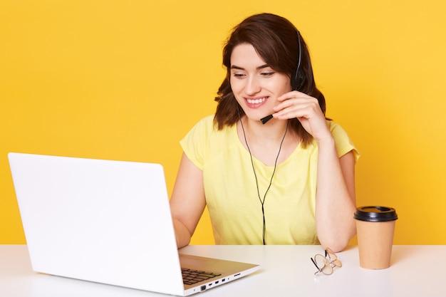 Jonge donkerharige meisje in koptelefoon met microfoon zit aan tafel met laptop, werkt op toetsenbord en praten met klant, koffie drinken, heeft een aangename glimlach, het dragen van gele t-shirt. Premium Foto