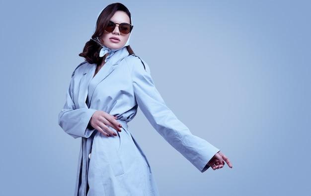 Jonge elegante donkerbruine vrouw in jas en sjaal het stellen in studio Premium Foto