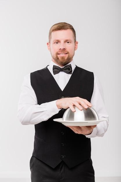 Jonge elegante ober in zwart vest en bowtie cloche met maaltijd te houden terwijl hij geïsoleerd voor de camera staat Premium Foto