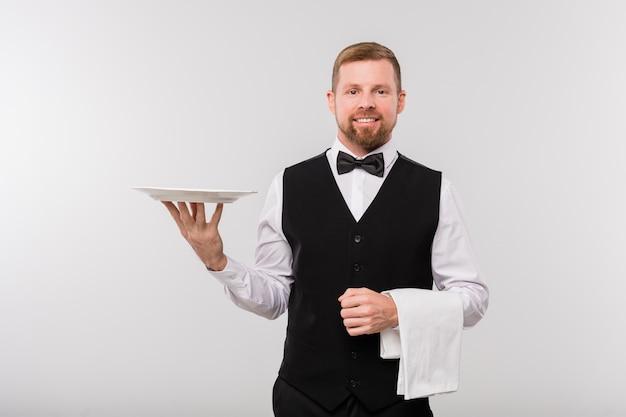 Jonge elegante ober in zwart vest en bowtie die witte handdoek en plaat houdt terwijl hij geïsoleerd voor camera staat Premium Foto
