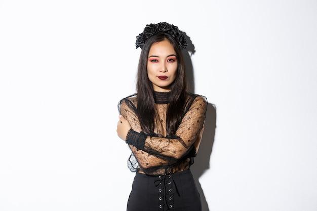 Jonge elegante vrouw in stijlvolle gotische jurk en krans, haar lichaam omhelst en brutaal naar de camera kijken, halloween kostuum van ondode weduwe dragen, staande op witte achtergrond. Gratis Foto