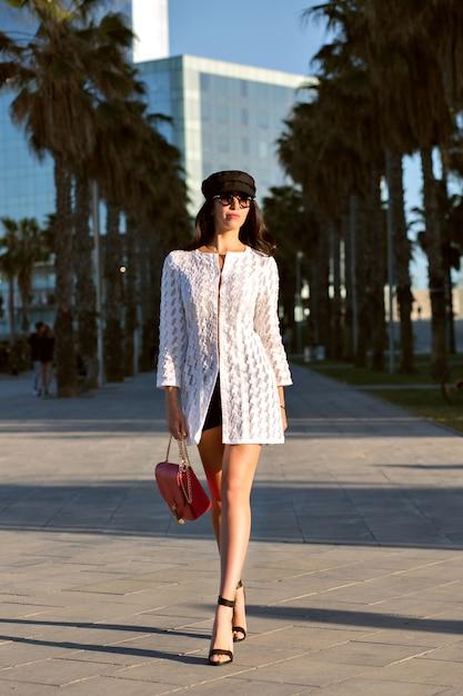 Jonge elegante vrouw lopen alleen, trendy elegante outfit en accessoires, midden leeftijd sexy dame, getinte kleuren, palmen steegjes. Gratis Foto
