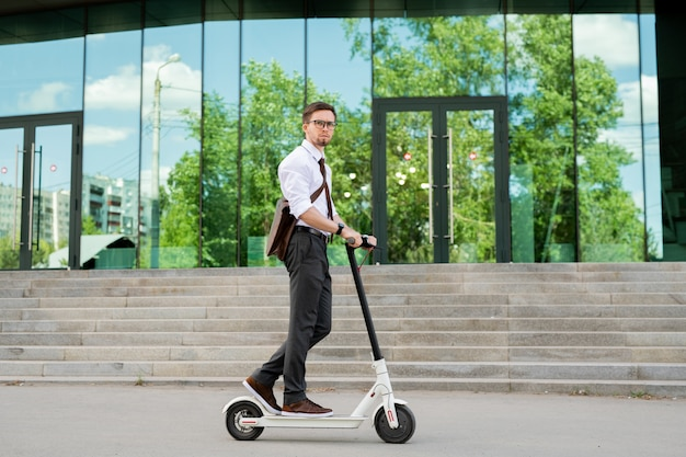 Jonge elegante zakenman permanent op scooter en verhuizen naar café of huis op de weg met de buitenkant van het gebouw op de achtergrond Premium Foto