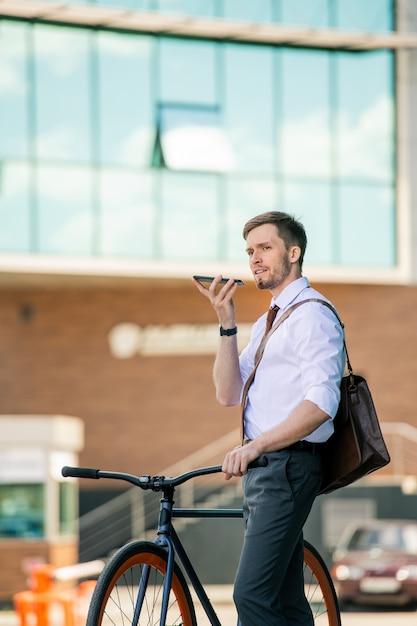 Jonge elegante zakenman spraakbericht opnemen op smartphone zittend op de fiets tegen buitenkant van modern gebouw Premium Foto