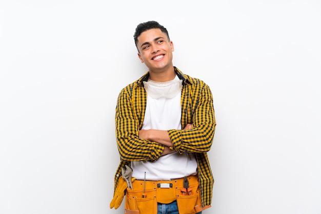 Jonge elektricienmens over geïsoleerde witte muur die omhoog terwijl het glimlachen kijkt Premium Foto
