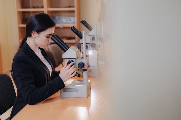 Jonge emotionele aantrekkelijk meisje aan de tafel zitten en werken met een microscoop Premium Foto
