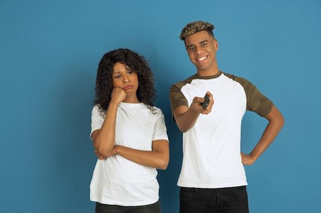 Jonge emotionele man en vrouw in witte vrijetijdskleding die zich voordeed op blauw. Gratis Foto