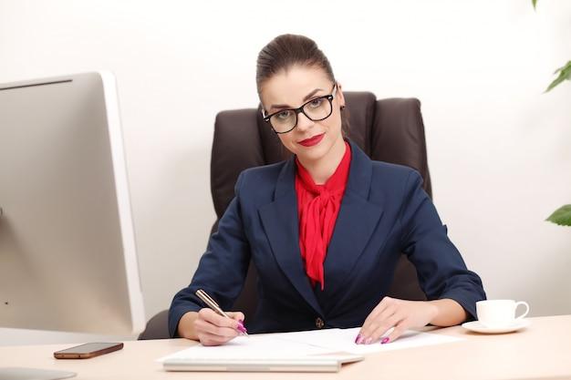 Jonge en aantrekkelijke bedrijfsvrouw die in bureau werkt Premium Foto