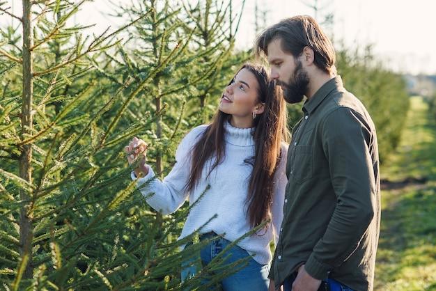 Jonge en gelukkige familie kerstboom kiezen op plantage wintervakantie voorbereiden. Premium Foto