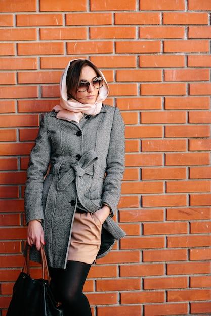 Jonge en mooie vrouw die zich voordeed op een rode bakstenen muur Gratis Foto