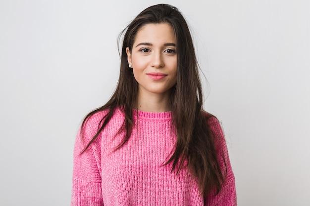 Jonge en mooie vrouw in roze warme trui, natuurlijke uitstraling, glimlachen, portret op, geïsoleerd, lang haar Gratis Foto