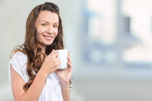 Jonge en mooie vrouwenportret het drinken koffie Premium Foto