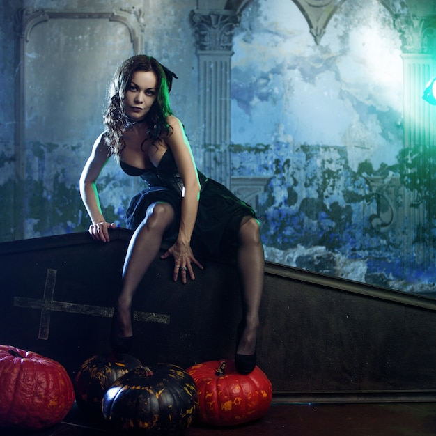 Jonge en sexy vrouw, beeld van heksen in een begraafplaatszitting op dekselkist. Premium Foto
