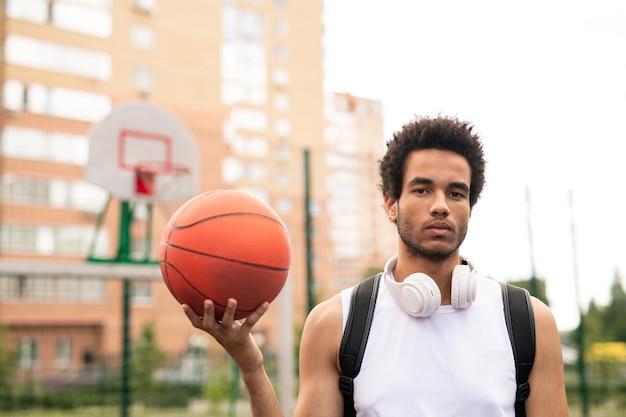Jonge ernstige actieve mannelijke basketballer in de witte bal van de t-shirtholding terwijl status op speelplaats Premium Foto