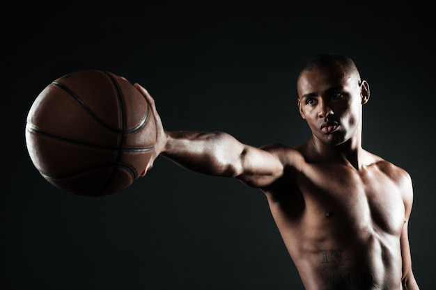 Jonge ernstige de holdingsbal van de basketbalspeler met één hand Gratis Foto