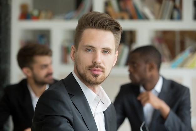 Jonge ernstige zakenman die camera op vergadering, headshotportret bekijkt Gratis Foto