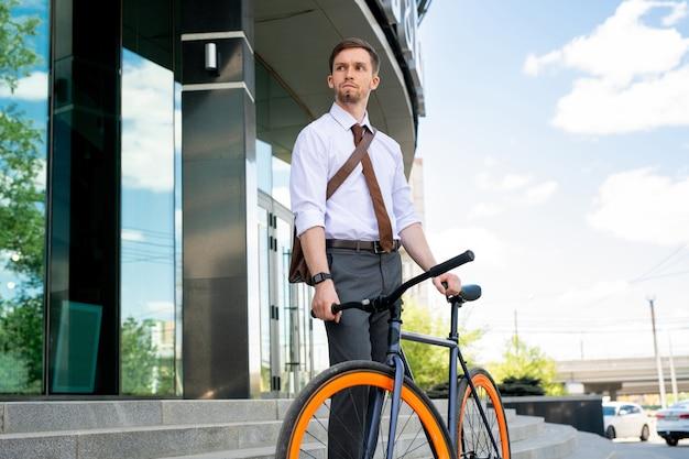 Jonge ernstige zakenman gaat met de fiets terwijl hij op de achtergrond van de trap en de buitenkant van een modern gebouw staat Premium Foto