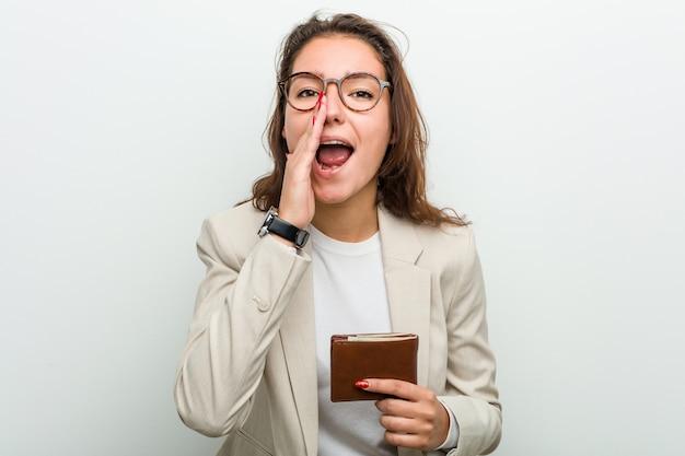 Jonge europese bedrijfsvrouw die portefeuille schreeuwen opgewekt aan voorzijde houden. Premium Foto