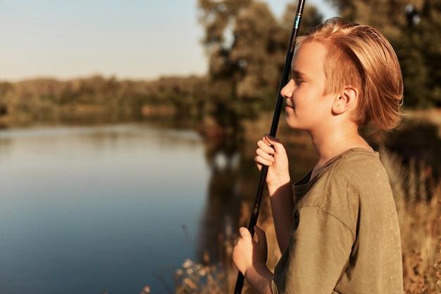 Jonge europese blonde jongen vissen in zonnige zomerdag, kijken in de verte, genieten van zijn vrije tijd, groene t-shirt dragen, staande op de oever van de rivier in de buurt van water. Gratis Foto