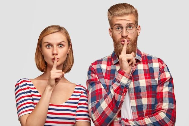 Jonge europese vriend en vriendin, stilte teken tonen, kijkt met verbaasde uitdrukkingen, toon stil gebaar Gratis Foto
