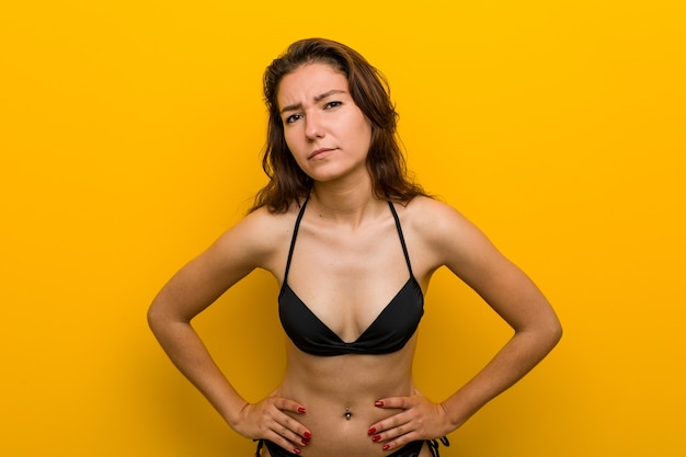 Jonge europese vrouw die bikini draagt die zeer boos iemand uitscheldt. Premium Foto