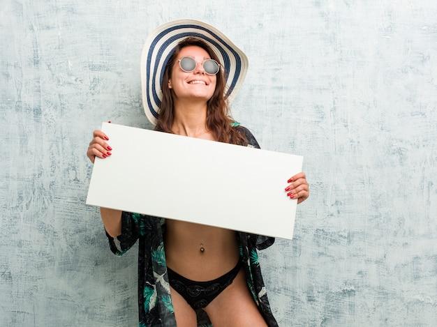 Jonge europese vrouw die bikini draagt en een aanplakbiljet houdt Premium Foto
