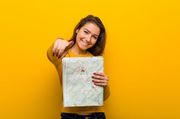 Jonge europese vrouw die een kaart vrolijke glimlachen houdt die aan voorzijde richten. Premium Foto