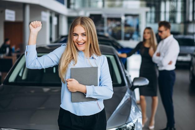 Jonge familie die een auto in een autotoonzaal kiest Gratis Foto