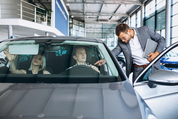 Jonge familie die een auto in een autotoonzaal koopt Gratis Foto