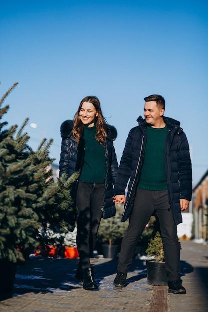 Jonge familie die kerstmisboom in een serre kiest Gratis Foto