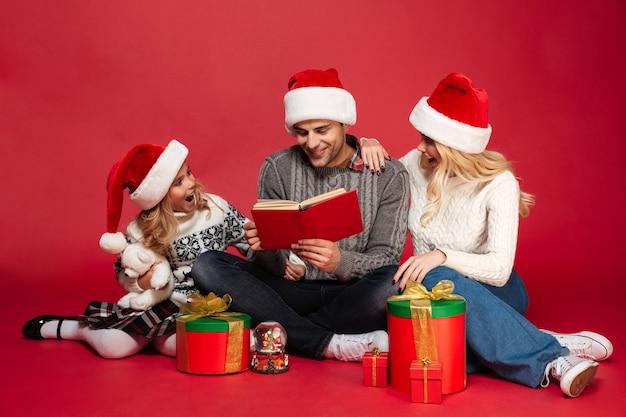 Jonge familie die kerstmishoeden geïsoleerd zitten dragen Gratis Foto