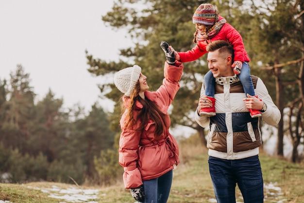 Jonge familie die samen in bos in de wintertijd loopt Gratis Foto