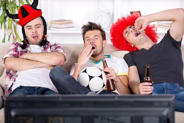 Jonge fans vielen in slaap tijdens het kijken naar een voetbalwedstrijd. Premium Foto