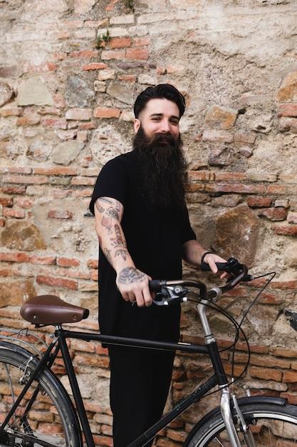 Jonge fietser die zich tegen oude bakstenen muur bevindt die camera bekijkt Gratis Foto