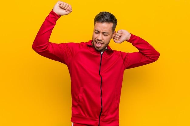 Jonge filipijnse fitness man viert een speciale dag, springt en hef armen met energie. Premium Foto