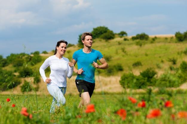 Jonge fit paar joggen in de natuur Premium Foto