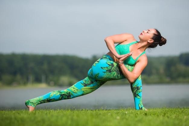 Jonge fit vrouw beoefenen van yoga buiten in park Gratis Foto