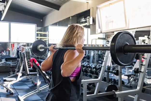 Jonge fit vrouw op de sportschool doet zware oefening. vrouwelijke atleet in een fitnessruimte uit te werken met barbell Premium Foto
