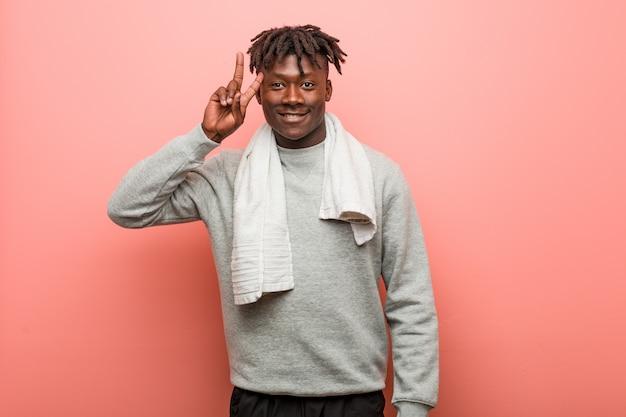 Jonge fitness afrikaanse zwarte mens die overwinningsteken toont en breed glimlacht. Premium Foto